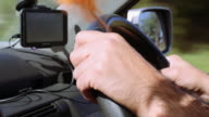 4K footage: Close up of the hands of a man driving with a GPS at the background