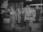 Footage from 1942 of German military officers on steps crowd in background / German officers walking through gate towards camera with Pierre Laval /...
