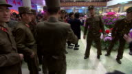 Footage from a flower show in North Korea showing soldiers posing for photos in front of the colourful backdrop