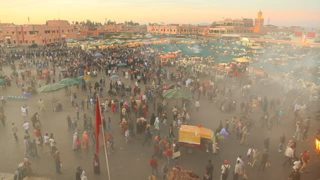 Footage from elevated viewpoint of the bustle main square of Jemaa El Fna in Marrakech city during sunset with people walking in every direction during travel vacations in Morocco.