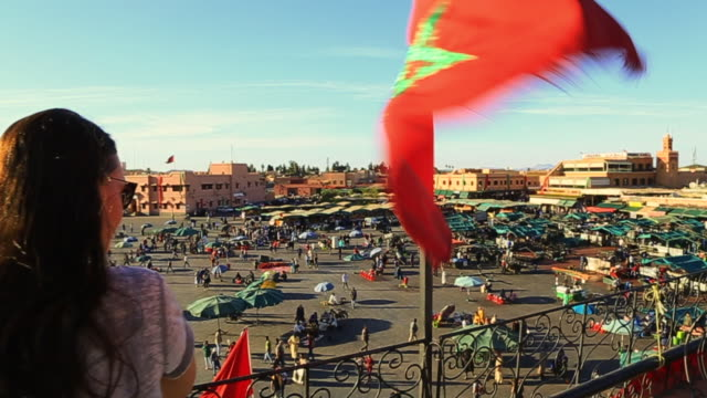Footage from elevated viewpoint of traveler girl contemplating the bustle main square of Jemaa El Fna in Marrakech city during sunset with people walking in every direction during travel vacations in Morocco.