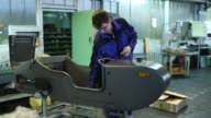 Footage from inside the Irbit Motorworks Factory in Irbit Russia December 10 2015 Shots CU of orange motorbike with worker in the background slightly...