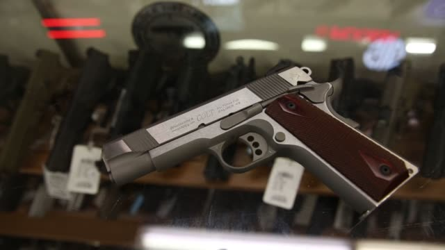Footage of a gun store that sells all types of guns and rifles in Orem Utah on August 12 2016 Shots CU of handgun zoom out to table clerk picks up...