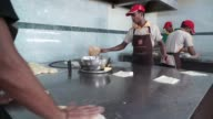 Footage of a kitchen of a restaurant in Kuala Lumpur Malaysia on September 29 2015 Shots shot of griddle as two workers cook tighter shot of cook...