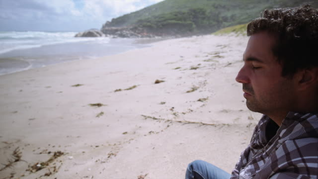 4K footage of a man with eyes closed and seating on the beach, Wilson Promontory, Victoria, Australia