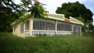 Footage of an abandoned house in the town of Dorado Puerto Rico on July 9 2017 Shots wide shot of close4d home behind fence CU of fence pan left...