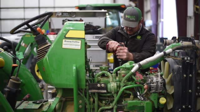 Footage of an employee working on a John Deere Tractor at a dealership in Waco TX on November 20 2017 Photographer Sergio Flores Shots MS of worker...