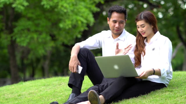 4K Footage of asian Businessman and Businesswoman with casual suit working with technology laptop at the outdoor park