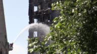 Footage of hoist and hose spraying water on Grenfell Tower Ambulances and Fire trucks drive through the cordons
