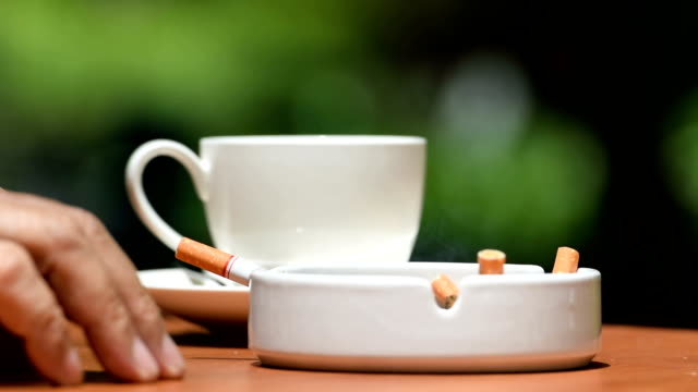 Footage of man having conversation while smoking cigarette and drinking coffee outdoor