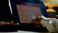 Footage of man holding lit and smoking cigarette between fingers and working on a laptop computer