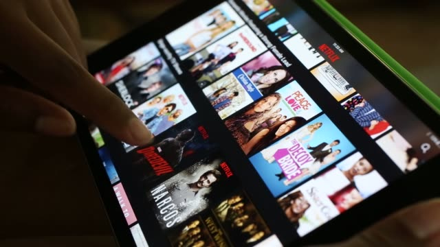 Footage of Netflix being scrolled through on a tablet in Peoria Illinois on July 11 Shots over the shoulder shot of hands on Netflix app on tablet...