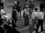 Footage of several newspaper boys selling papers on a crowded pedestrian corner /