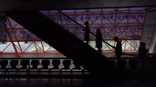 4K Footage of silhouette People moving on flat escalators in the office building.