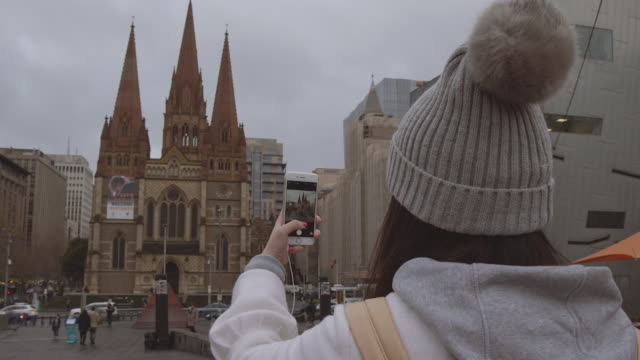 4K footage of tourist, from the back, taking a photo with her smartphone, Melbourne, Australia