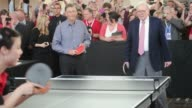 Footage of Warren Buffet and Bill Gates playing table tennis during a Berkshire Hathaway Shareholder's event outside Borsheims Jewelery Store / Gates...