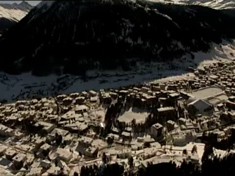 footage shot in a helicopter / overview of Davos Switzerland / aerial view of the Swiss Alps / various angles and views of snow covered Davos...