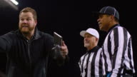MS LA DS SLO MO Football coach arguing with referees on sideline during game