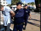 Euro 2004 England fans deported ITN PORTUGAL Albufeira EXT Deported England fan lead along to court with bowed head as swears at cameraman and...