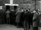 Football fans queue up to enter Old Trafford football stadium. 1964.