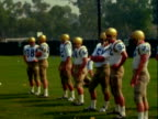 UCLA football performs various practice drills including tackling passing and punting / coach talking to team members / player puts helmet on and...