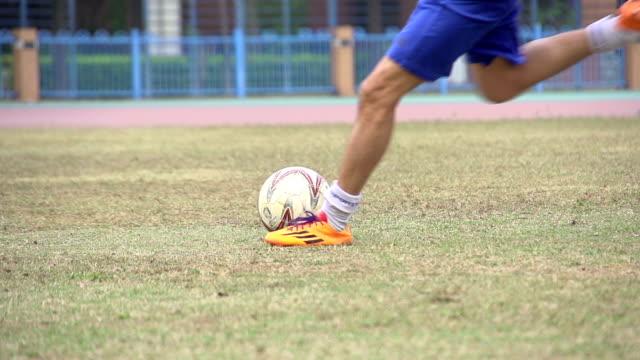 Football-Spieler treten den Ball auf dem Platz