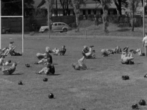 Football players in uniform lying on field doing exercise drills stretching back sit ups coaches overlooking Athletics American football