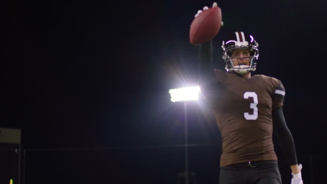 MS SLO MO Football quarterback walking across field at night with ball celebrating