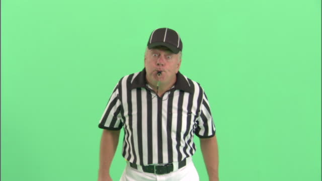 MS, Football referee blowing whistle in studio, portrait