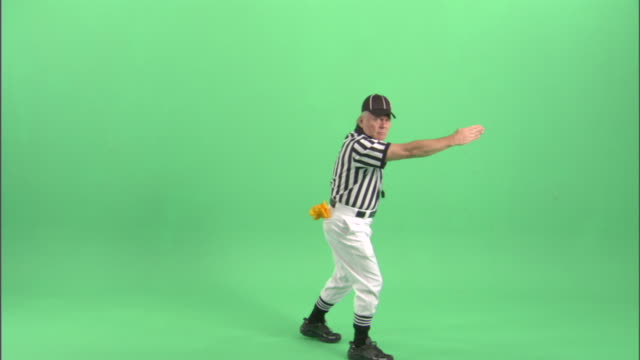 WS, Football referee signaling 'illegal motion' in studio, portrait