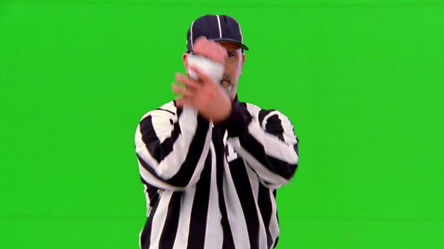 CHROMA KEY MS football referee with whistle in mouth signaling 'holding/illegal use of hands' penalty