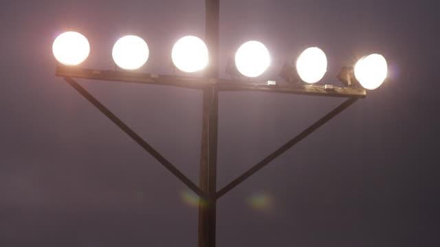 Football stadium lights, six lights on a bar attached to a pole close