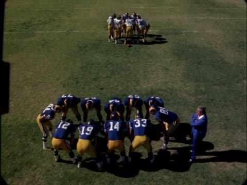 Football teams huddle before a field goal kick.