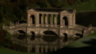 A footbridge casts a reflection on a pond in a park. Available in HD.