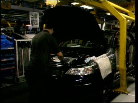 Bridgend Assembly area inside Ford engine plant PAN TMS Workers working to assemble engines MS Another ditto Engine along on production line as...
