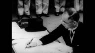 / Foreign Affairs Minister Mamoru Shigemitsu sits at desk on board USS Missouri to sign Japanese surrender documents / General Douglas MacArthur then...