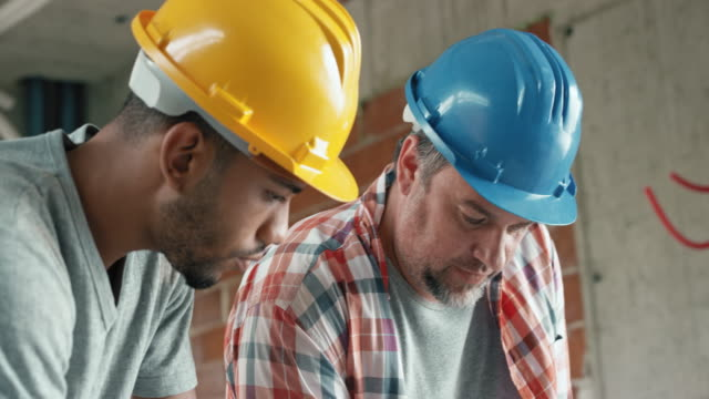Foreman giving instructions to his worker, showing him details on the plan on the table at the construction site