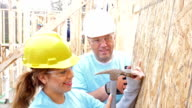 Foreman helps young volunteer as they build home for charity