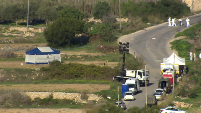 Forensics officers inspecting the scene of a car bomb attack in Bidnija Malta which killed investigative journalist Daphne Caruana Galizia