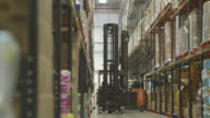 Forklift vehicles manoeuvre at a busy food distribution warehouse in the UK.
