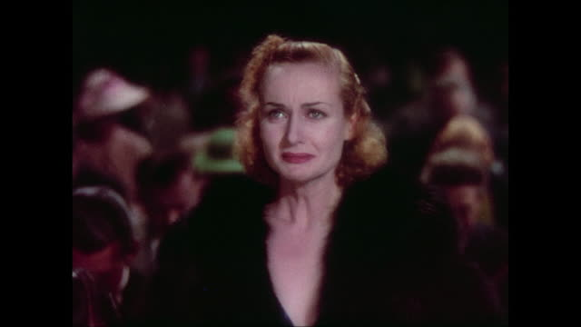 Formally dressed audience bow their heads in respect as distressed woman (Carole Lombard) stands bewildered