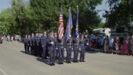 Formation of military Air Force personnel march down the street in small town parade.