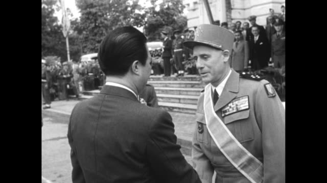 Former emperor Bao Dai wearing sunglasses stands with French general as he reviews an honor guard upon his arrival in Hanoi / CU Bao Dai with members...