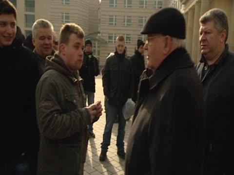 Former Soviet leader Mikhail Gorbachev greets men in Berlin