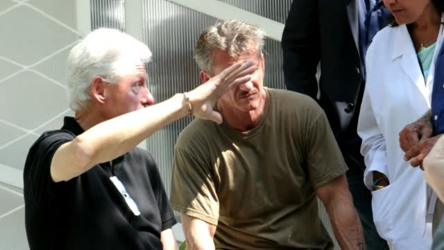 Former US President Bill Clinton and US actor Sean Penn visit a relief organization in Haiti