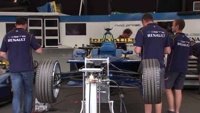 Formula E at Battersea and interviews ENGLAND London Battersea Park EXT Alain Prost along by garages / mechanics working next to Formula E cars