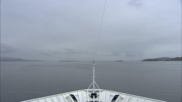Forward tracking shot from the prow of a passenger ferry as it travels along the Norwegian coastline.