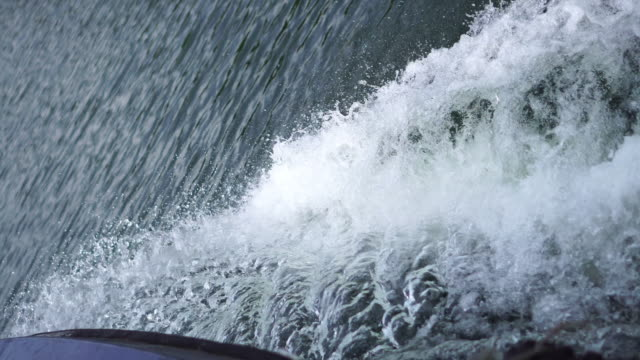 Forward tracking shot of water splashing from port side of boat