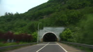 Forward tracking shots along a road and into a tunnel in China.