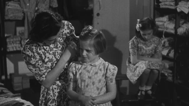 1950 MONTAGE Foster mother tying a bow into an orphan's hair as they finish dressing to go out / United Kingdom
